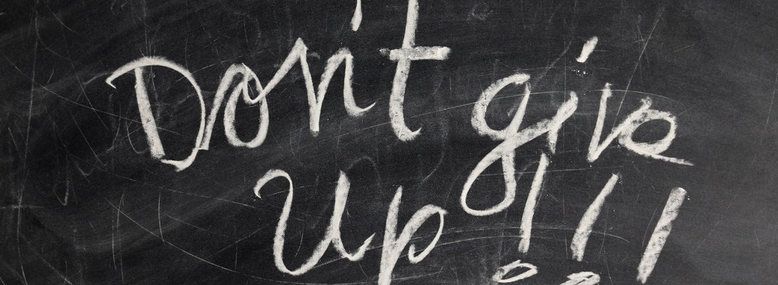 "Image of a well used chalkboard with the words ""Don't give up!!!"" written on it in white chalk, in script lettering."